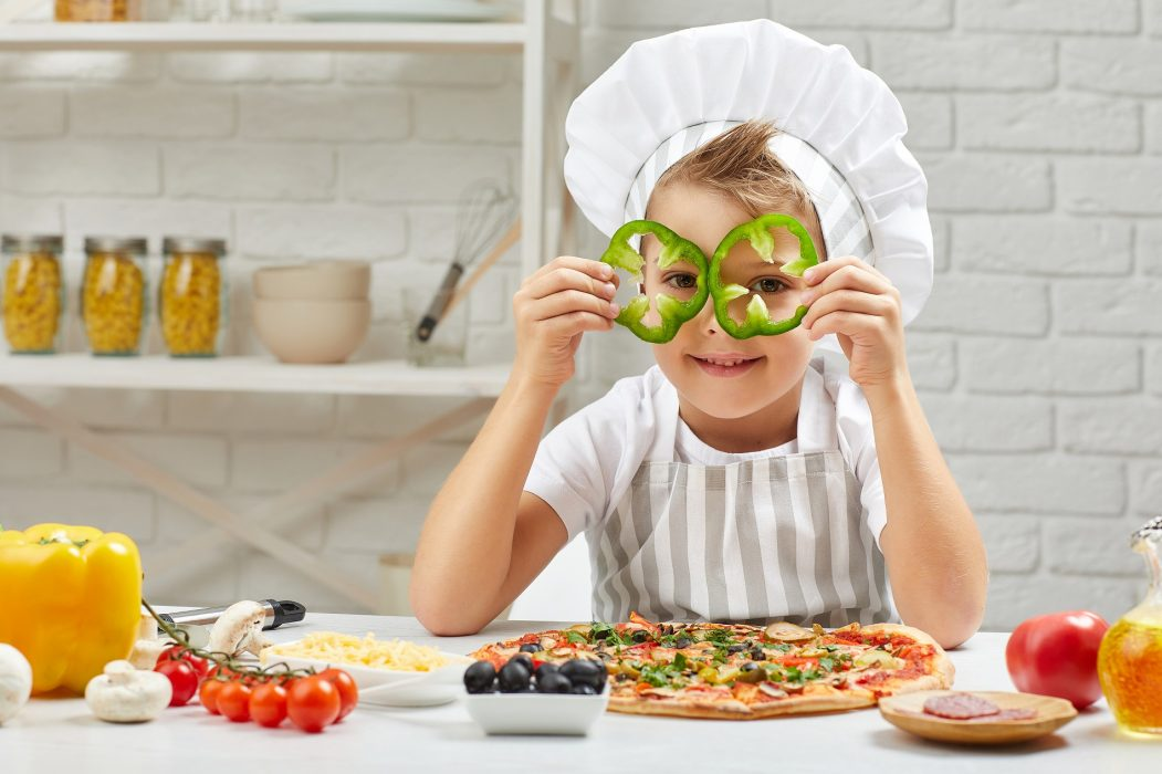 little boy in chef hat and an apron cooking pizza in the kitchen. the child holding green bell peppers . having fun