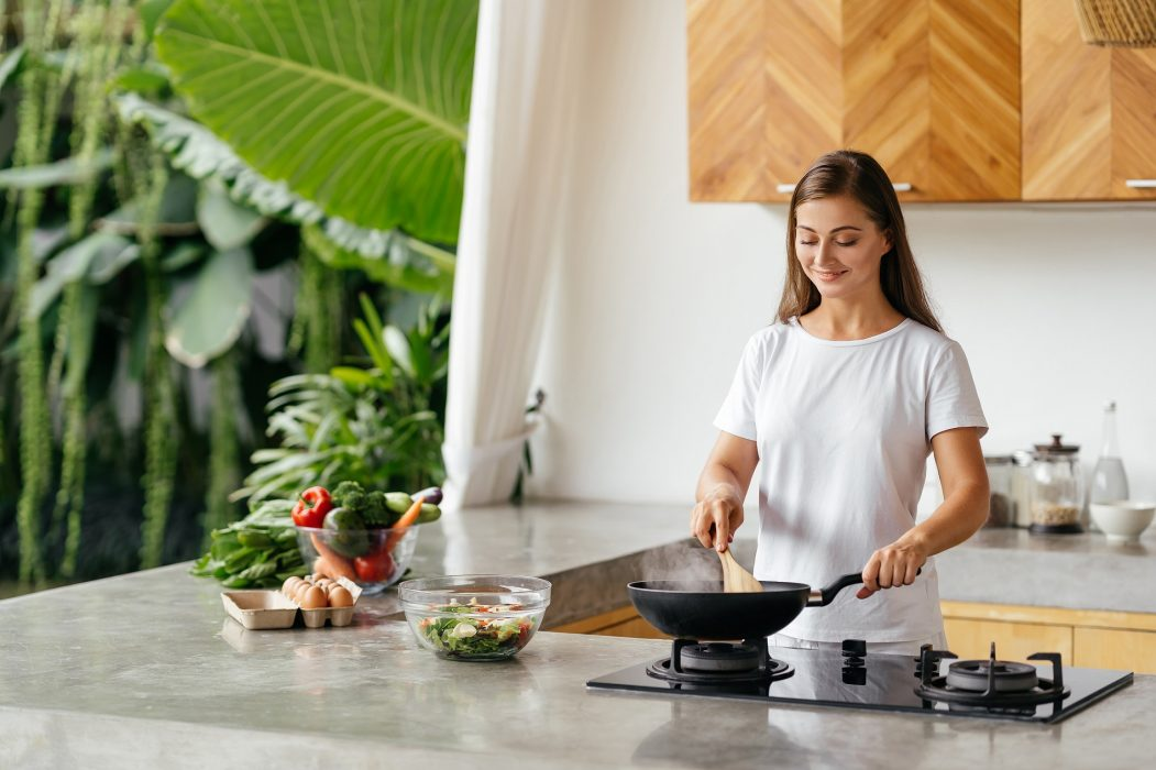 Young woman cooking in the open kitchen. Healthy Food. Dieting Concept. Healthy Lifestyle. Cooking At Home. Prepare Food